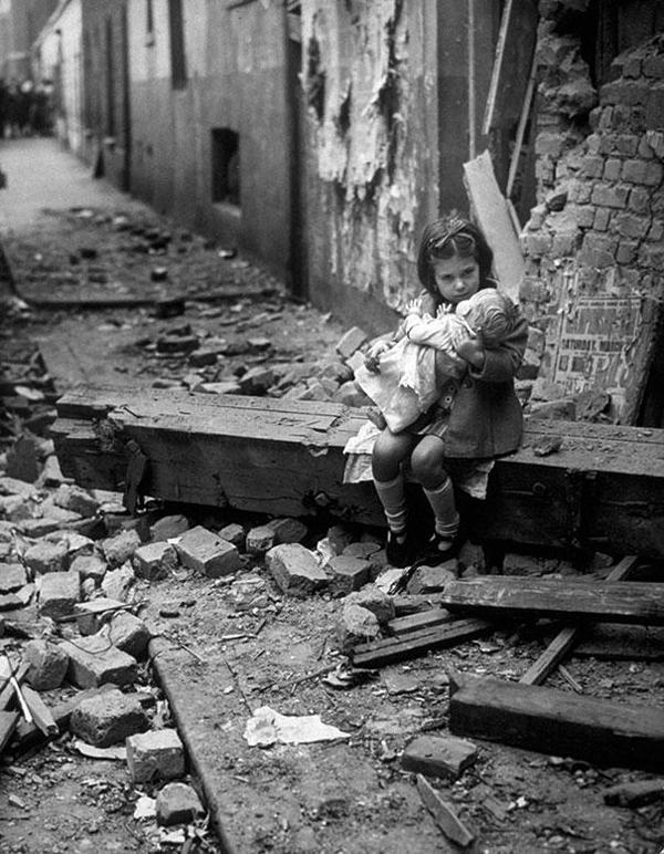 17-Niña-con-su-muñeca-sentada-en-las-ruinas-de-su-casa-Londres-1940